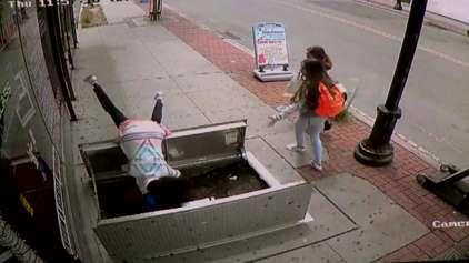 Mulher anda olhando para smartphone e cai dentro de buraco